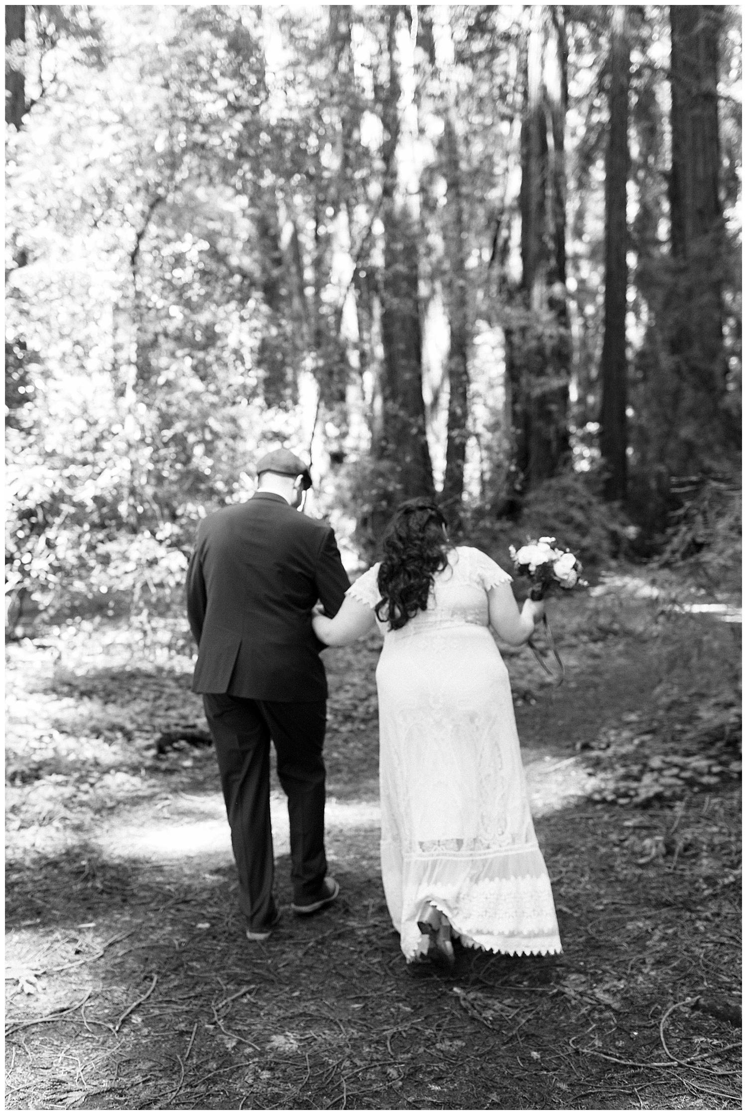 Bride and groom walk away following Henry Cowell redwoods wedding ceremony