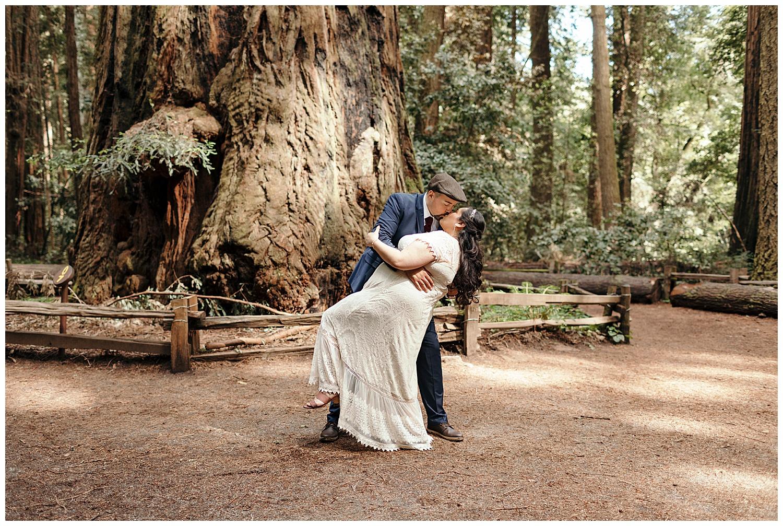 Groom dips bride in Henry Cowell redwoods after wedding