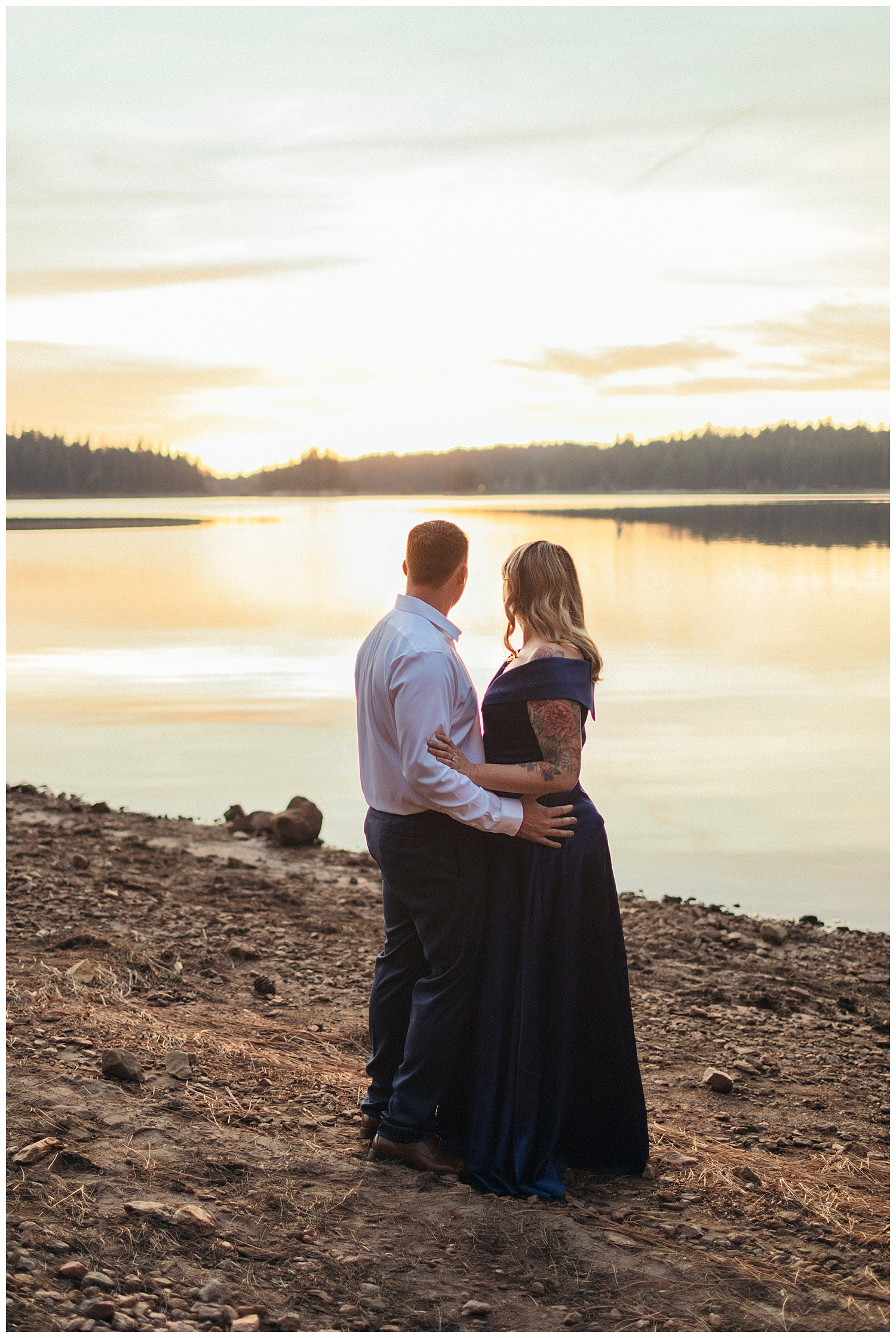couple stares at sunset over jenkinson lake in el dorado national forest