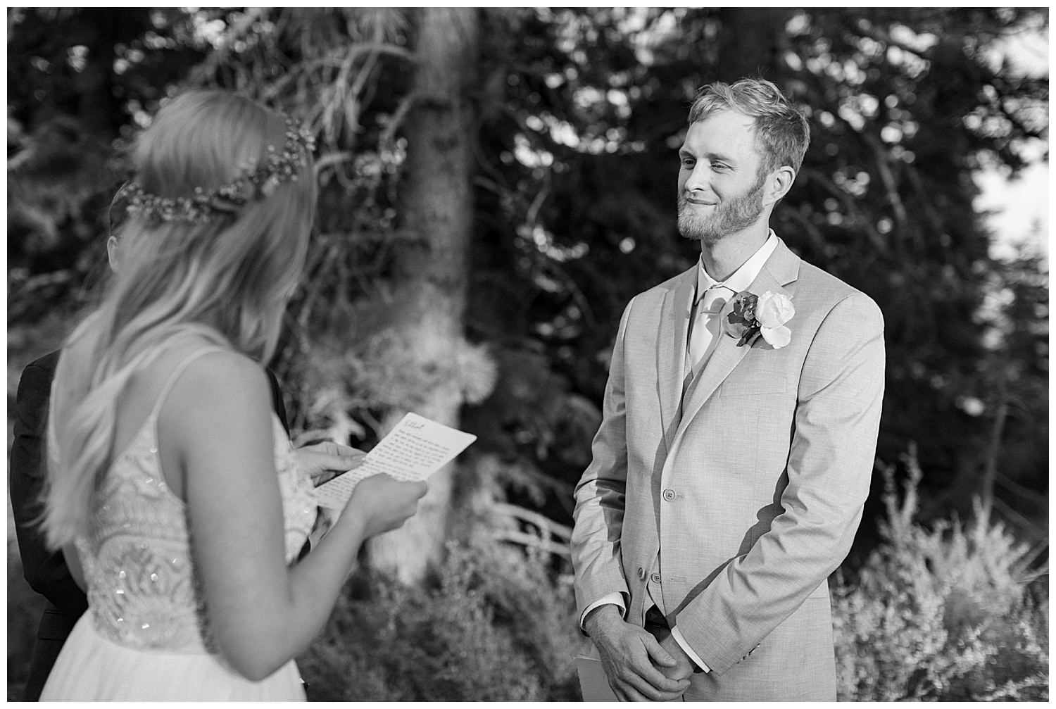 groom looks at bride while she reads vows in lake tahoe elopement