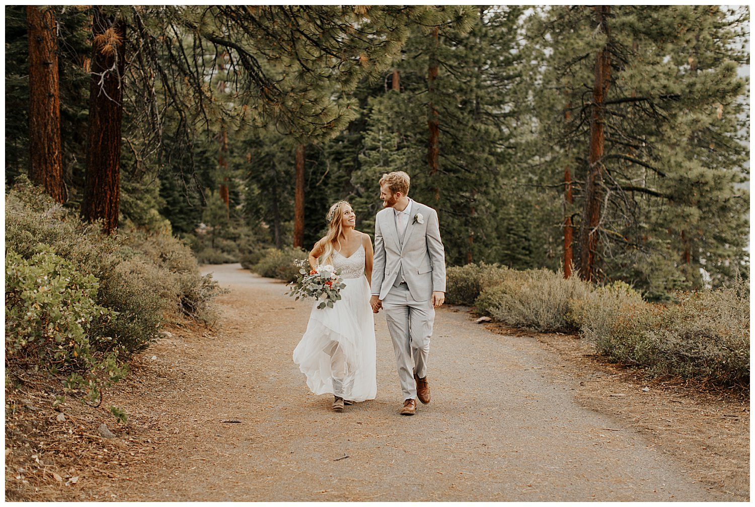 bride and groom share smiles walking in lake tahoe