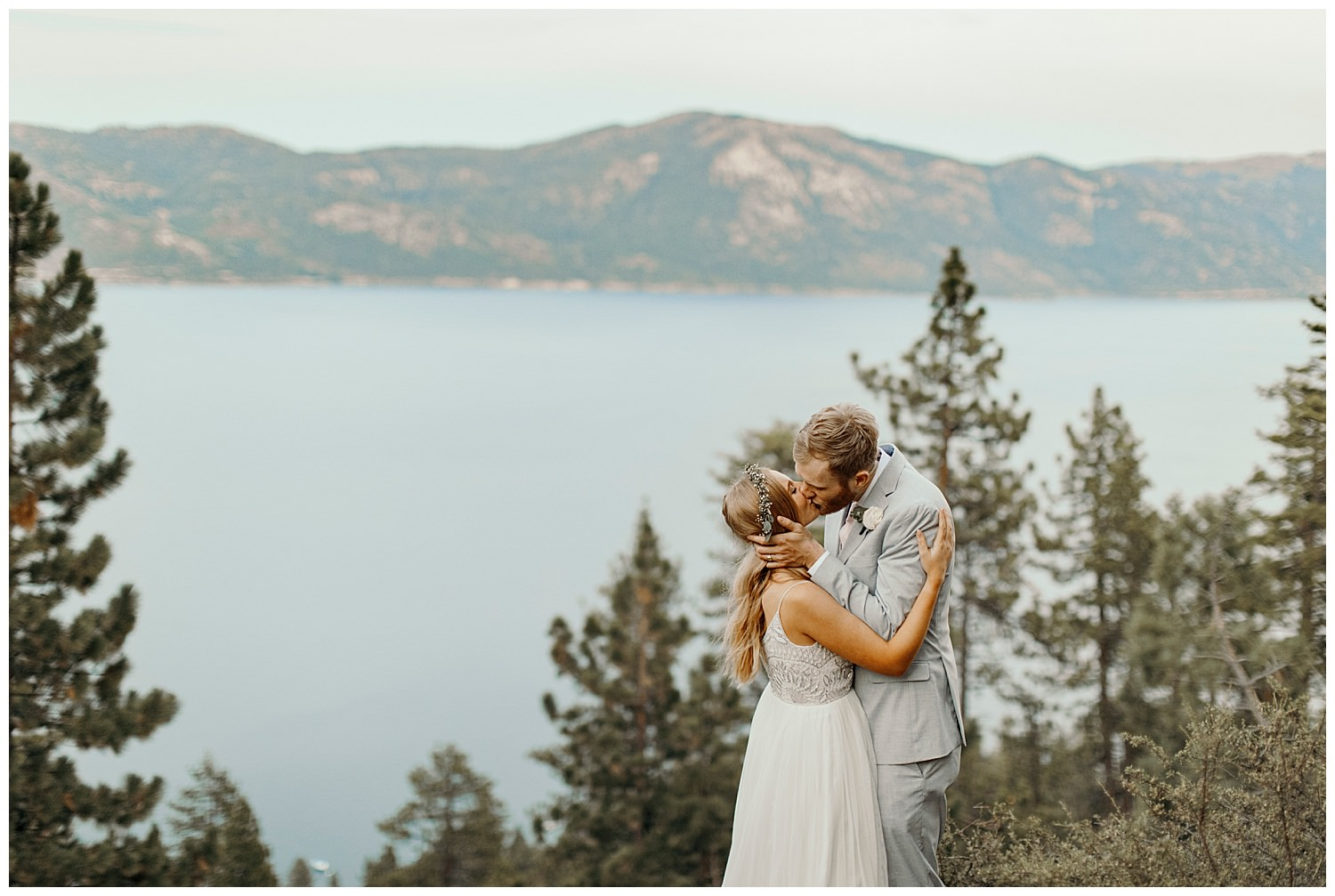 bride and groom kiss with lake tahoe and mountains behind them following their elopement
